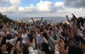 קבוצה גדולה מרימה ידיים לשמיים